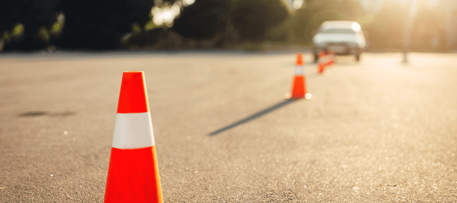 Traffic cone in focus with more cones and a car in the background blurred