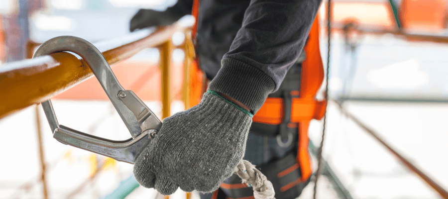 Construction worker wearing safety harness and safety line working on construction site, OSHA fall prevention and protection