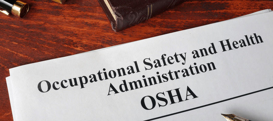Occupational Safety and Health Administration OSHA papers, a book, and a pen on wooden table