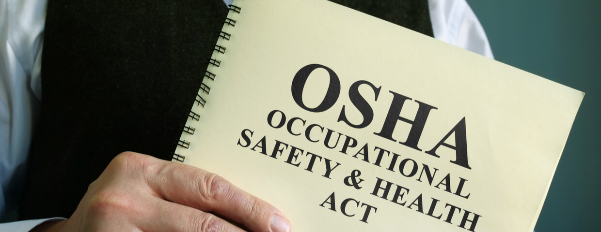 Man in suit holding OSHA booklet for training
