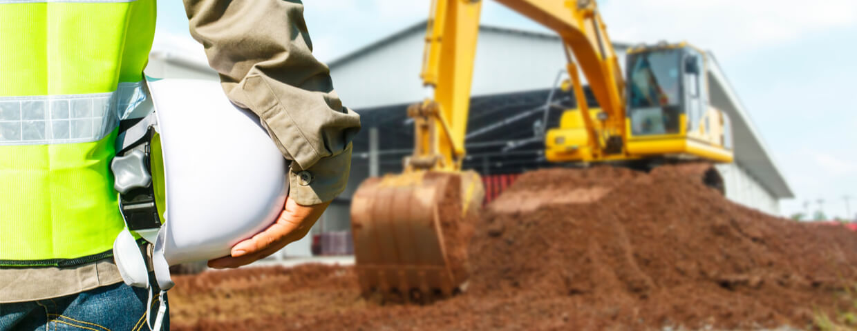 Engineer with hard hat and excavator machine at construction site