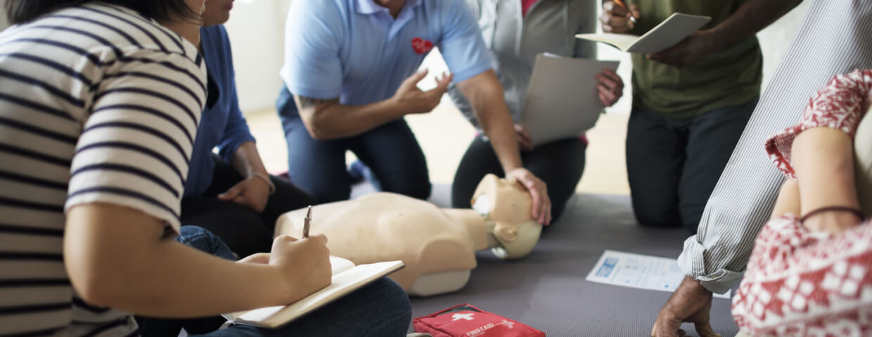 group of individuals doing a cpr training with instructor