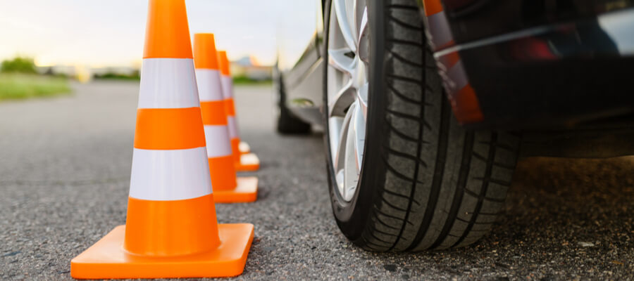 Car and traffic cones, driving school, defensive driving course concept