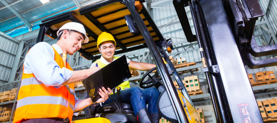 forklift driver discussing checklist with foreman in warehouse