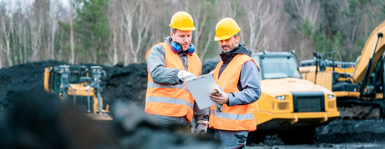 Workers in quarry, or surface mine, looking at a plan on clipboard