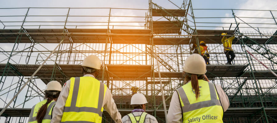 workers performing scaffolding risk analysis at construction site